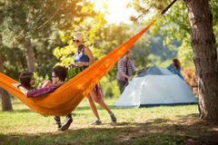 Female brings bottles of beer to friends in hammock Royalty Free Stock Photography