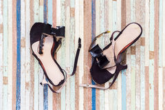 Female broken high heel shoes on grungy wooden background Royalty Free Stock Image