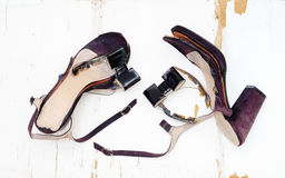 Female broken high heel shoes on grungy wooden background Stock Image