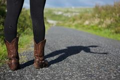 Female in brown boots standing on road Stock Photo