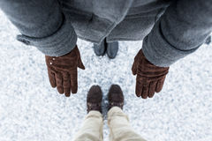 Female brown gloves and male casual boots standing on asphalt covered gritty snow surface. Cold Winter. Top view. Male and Female boots standing on asphalt Stock Photos
