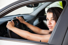 Female brunette driving with both hand on wheel Royalty Free Stock Photography