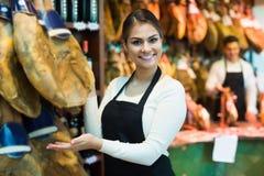 Female brunette selling jamon  in delicatessen store Royalty Free Stock Image