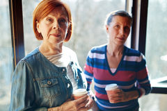 Female buddies. Aged female buddies wit hdrinks looking at camera Stock Photography