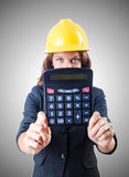 Female builder with calculator against gradient Stock Image