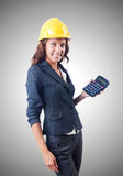 Female builder with calculator against gradient Royalty Free Stock Images