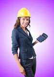 Female builder with calculator against gradient Royalty Free Stock Photos