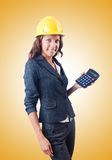 Female builder with calculator against gradient Royalty Free Stock Photo