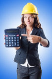 Female builder with calculator on white Stock Photo