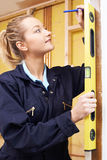 Female Builder Checking Work With Spirit Level Royalty Free Stock Image