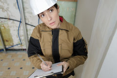 Female builder doing quotation for ceiling repair royalty free stock photography