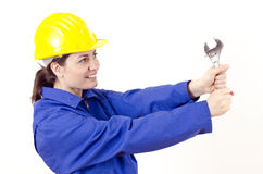 Female builder with helmet and big wrench. Female builder with helmet and wrench Royalty Free Stock Image