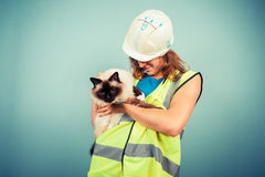 Female builder holding a cat Royalty Free Stock Photos
