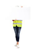 Female builder holding empty banner and covering her face Stock Photos