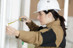 Female builder measuring wall Stock Photography