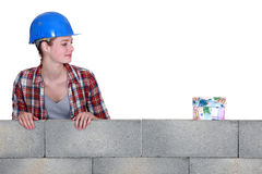 Female builder with money Royalty Free Stock Image