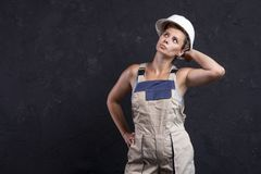 Female builder is posing for camera in studio. Portrait of beautiful woman worker builder in uniform with white helmet stock image