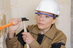 Female builder using hammer to remove plaster Royalty Free Stock Images