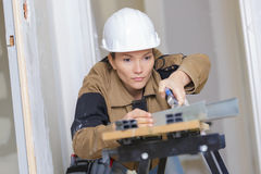 Female builder using machine electronic table saw cutting. Female builder using a machine electronic table saw cutting Royalty Free Stock Image