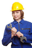Female builder with wrench. Female builder in overall with helmet and big wrench Stock Photo