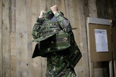 Female bulletproof vest. A female soldier puts on a bulletproof military vest Royalty Free Stock Photography