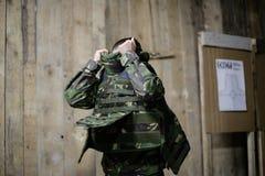 Female bulletproof vest. A female soldier puts on a bulletproof military vest Stock Images