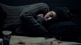 Female bum sleeping on dirty street feeling cold, poverty problem, refugee stock images