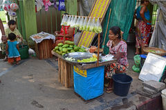 A female Burmese vendor selling cut fresh raw mango. At Yangon Myanmar. Whole full mango fruits are also available. The cut mangoes have mostly been packed into Stock Images