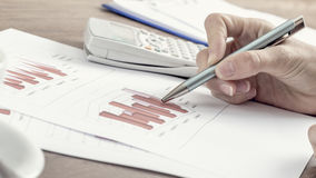 Female business accountant pointing to a graph with a pen Stock Photo