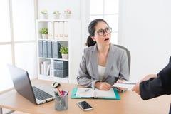 Female business boss received resignation letter. Beautiful elegant female business boss received resignation letter from office worker employee feeling shocked stock photos