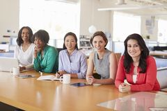 Female business colleagues in an office smiling to camera royalty free stock image