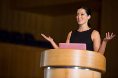 Female business executive giving a speech. At conference center Stock Photos
