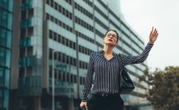 Female business executive hailing taxi Royalty Free Stock Photography