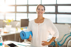Female business executive holding exercise mat Royalty Free Stock Photos