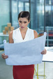 Female business executive looking at blueprint Royalty Free Stock Images