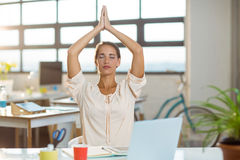 Female business executive performing yoga Stock Image