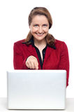 Female business executive pointing at laptop Stock Image