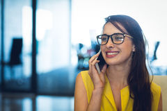 Female business executive talking on mobile phone Royalty Free Stock Image
