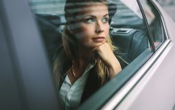 Female business executive travelling by a cab. Beautiful young businesswoman sitting on back seat of a car and looking outside the window. Female business royalty free stock photos