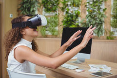 Female business executive using virtual reality headset Royalty Free Stock Images