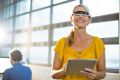 Female business executive in virtual reality video glasses using digital tablet Royalty Free Stock Photography