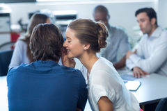 Female business executive whispering to her colleague. In office Stock Image