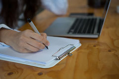 Female business executive writing on clipboard Royalty Free Stock Photography