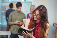 Female business executive writing in organizer Stock Photos