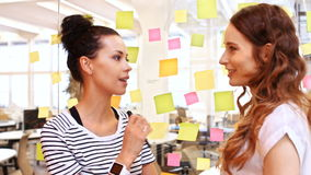 Female business executives interacting while reading sticky notes