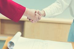 Female business handshake. Two young female executives making business handshake over successful contract, good for business or successful concept Stock Photography
