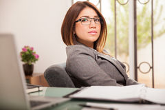 Female business manager. Pretty and confident Hispanic female boss sitting on her desk and looking serious stock image