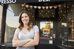 Female business owner stands outside cafe with arms crossed Stock Image