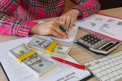 Female with Business plan, calculator, dollar banknote, spreadshee and pen on the table Stock Images