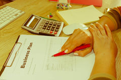 Female with Business plan, calculator and pen on the table. Woman working in office, sitting at desk, using computer Stock Image